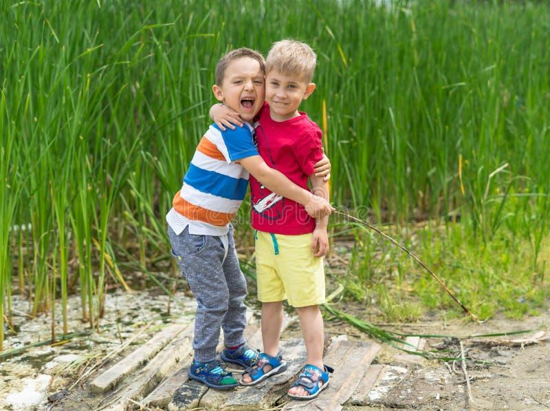 Zwei kleine Freunde umarmen sich am sonnigen Tag des Sommers Brot stockbilder