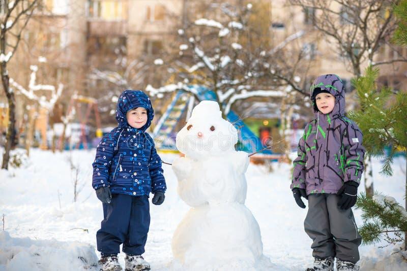 Zwei kleine Geschwisterkinderjungen, die einen Schneemann machen, Spaß mit Schnee, draußen am kalten Tag spielen und haben Aktive stockbild