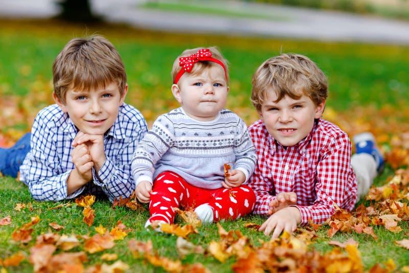Zwei kleine glückliche Kinderjungen mit neugeborenem Baby, nette Schwester Geschwister auf Gras im Herbstpark mit Gelbem und Rote lizenzfreie stockfotografie