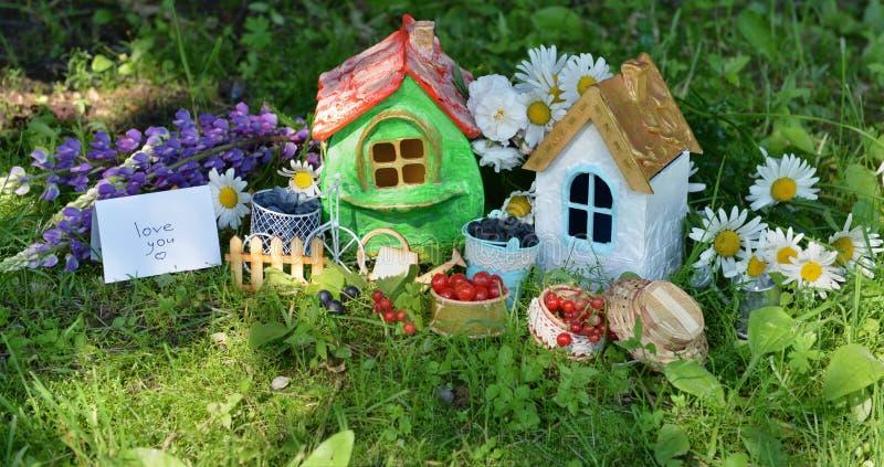 Zwei kleine Häuser mit Beere, Blumen und Text lieben Sie stockfotografie