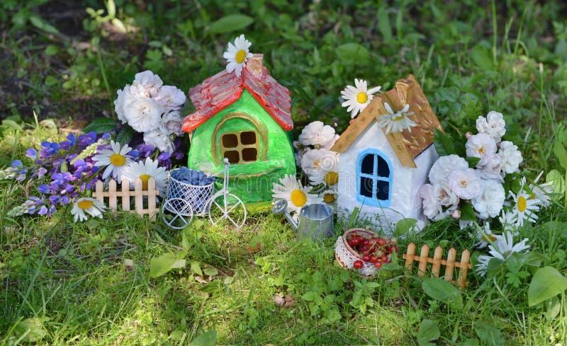 Zwei kleine Häuser mit Gartenblumen und Sommerbeeren stockfotografie