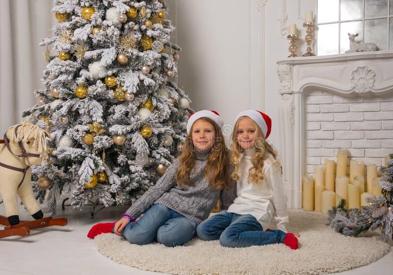 Zwei kleine hübsche Mädchen in den roten Weihnachtskappen sitzen nahe t stockbild