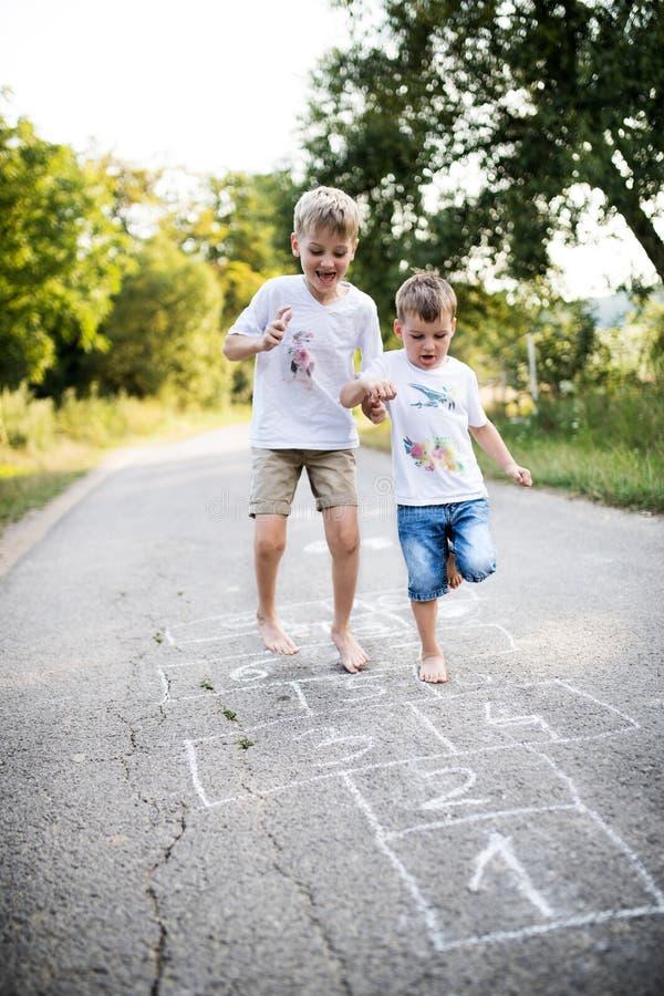 Zwei kleine Jungen, die auf einer Straße im Park an einem Sommertag hopscotching sind lizenzfreie stockfotos