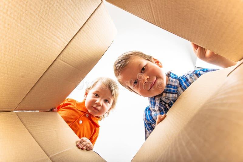 Zwei kleine Jungen, die Pappschachtel und das Schauen öffnen stockbilder