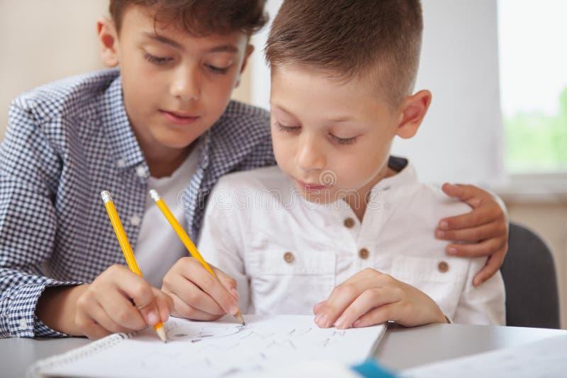 Zwei kleine Jungen, die zusammen in der Schule zeichnen stockfotografie
