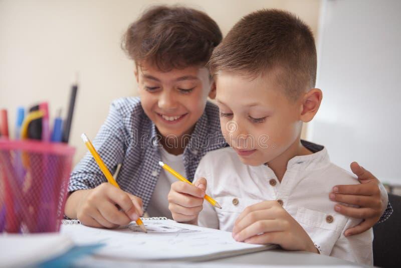 Zwei kleine Jungen, die zusammen in der Schule zeichnen stockbild