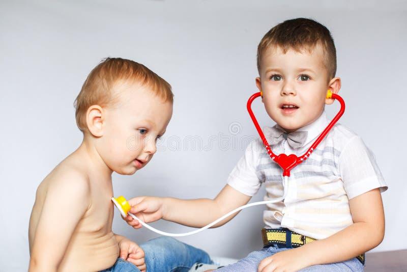Zwei kleine Jungen unter Verwendung des Stethoskops Kinder, die Doktor und Patienten spielen Überprüfen Sie den Herzschlag lizenzfreie stockfotografie