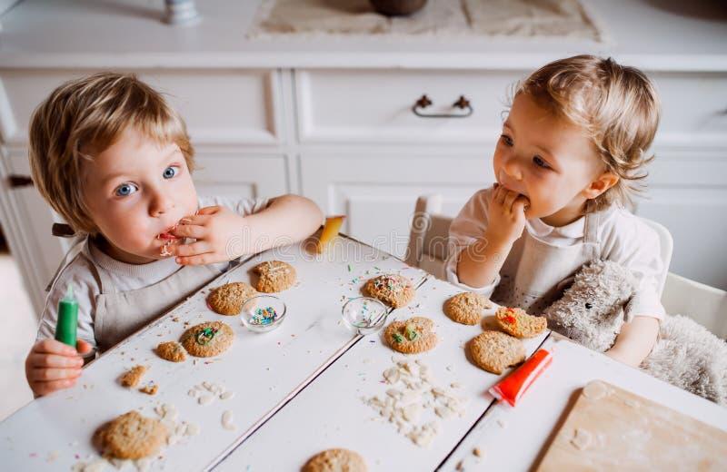 Zwei kleine Kleinkindkinder, die am Tisch sitzen, zu Hause Kuchen verzieren und essen stockfotos