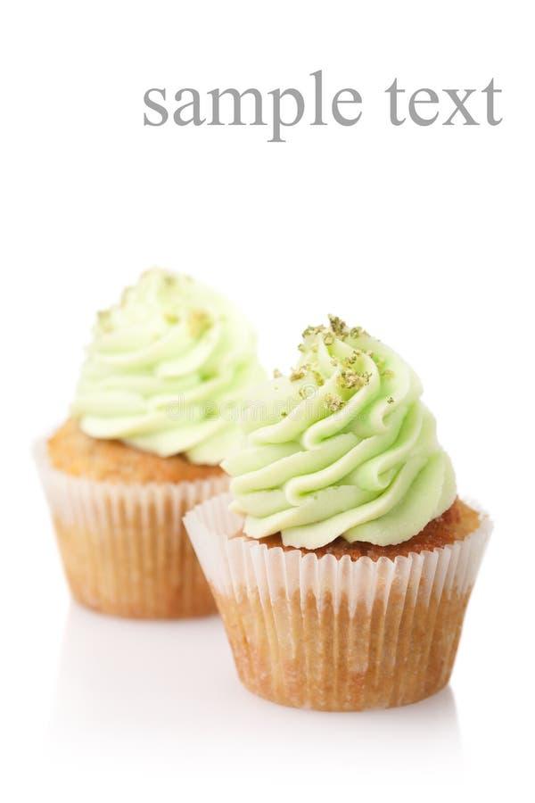Zwei kleine Kuchen mit der grünen Creme lokalisiert auf weißem Hintergrund stockfotografie