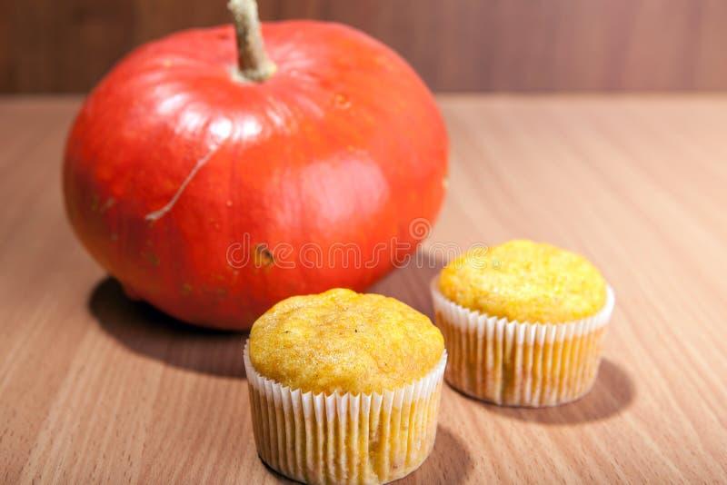 Zwei kleine Kuchen und Kürbis auf hölzerner Beschaffenheitstabelle lizenzfreies stockfoto