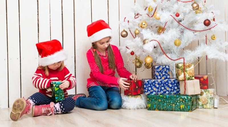 Zwei kleine Mädchen öffnen die Weihnachtsgeschenke, die auf dem Boden sitzen stockfotografie