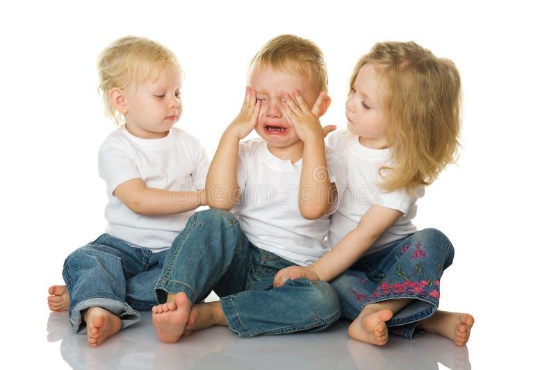 Zwei kleine Mädchen beruhigen den schreienden Jungen stockfotografie