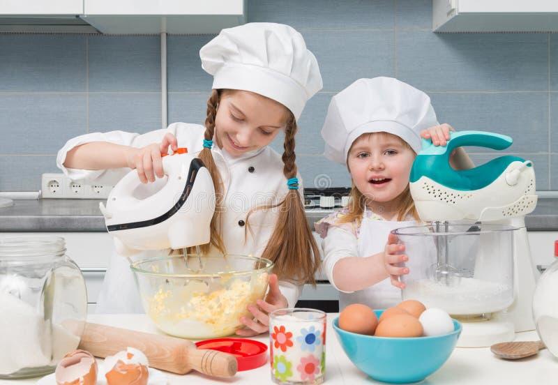 Zwei kleine Mädchen in der Chefuniform mit Bestandteilen auf Tabelle stockbilder
