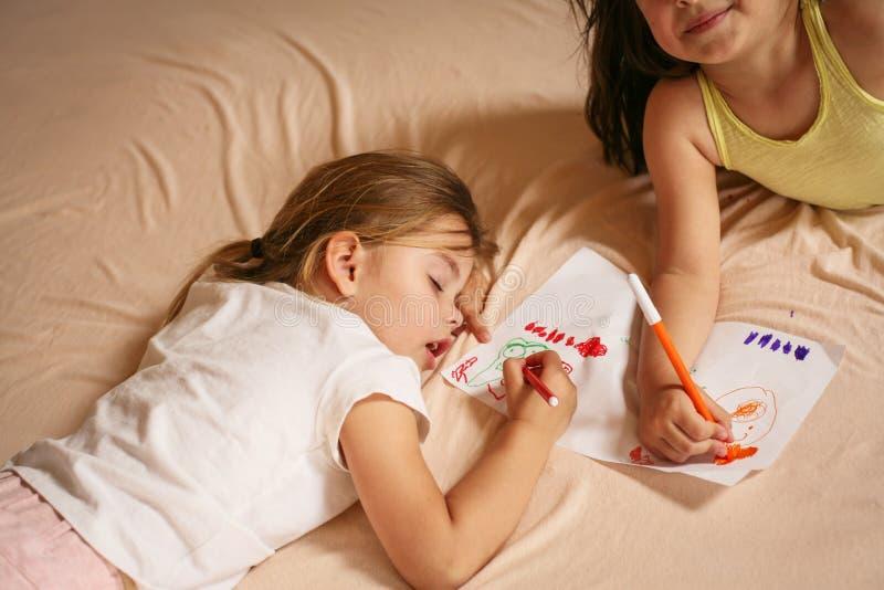 Zwei kleine Mädchen, die auf Bett schreiben lizenzfreie stockfotos