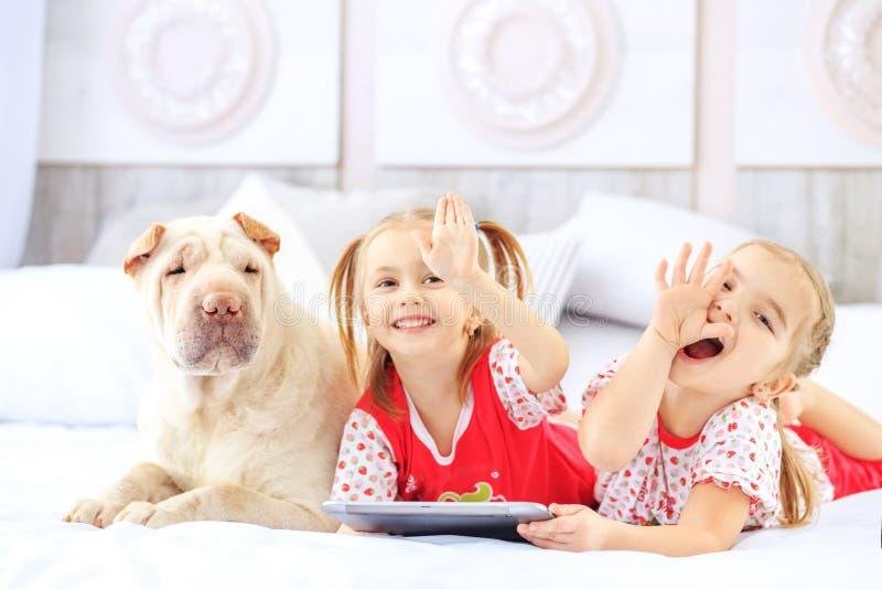 Zwei kleine Mädchen, die auf dem Bett mit einer Tablette liegen Hund Das concep lizenzfreie stockfotos