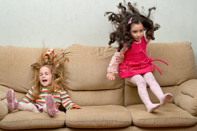 Zwei kleine Mädchen, die auf Sofa springen