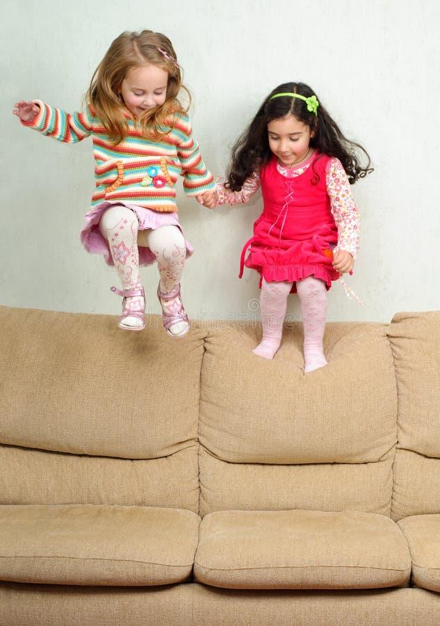 Zwei kleine Mädchen, die auf Sofa springen lizenzfreie stockfotos