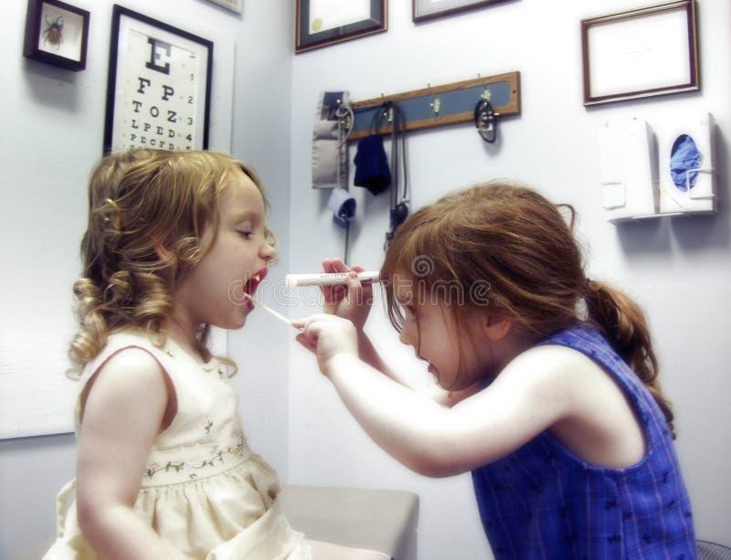 Zwei kleine Mädchen, die Doktor spielen lizenzfreie stockbilder
