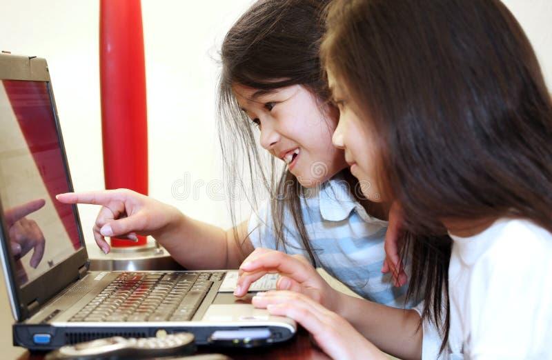 Zwei kleine Mädchen, die an einem Laptop arbeiten stockfoto
