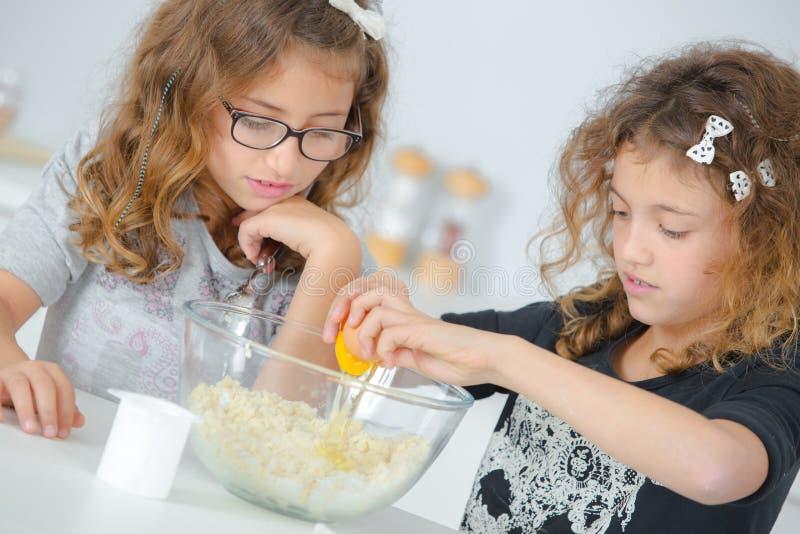 Zwei kleine Mädchen, die Kuchenmischung vorbereiten stockbild