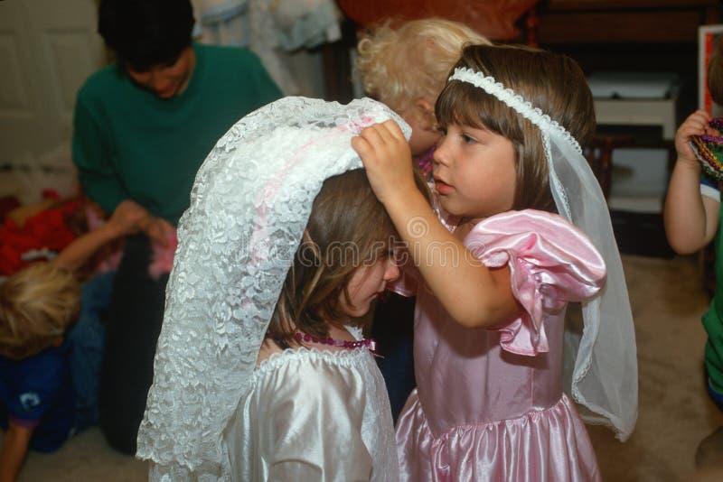 Zwei kleine Mädchen, die oben in den Hochzeitsausstattungen ankleiden stockfotografie