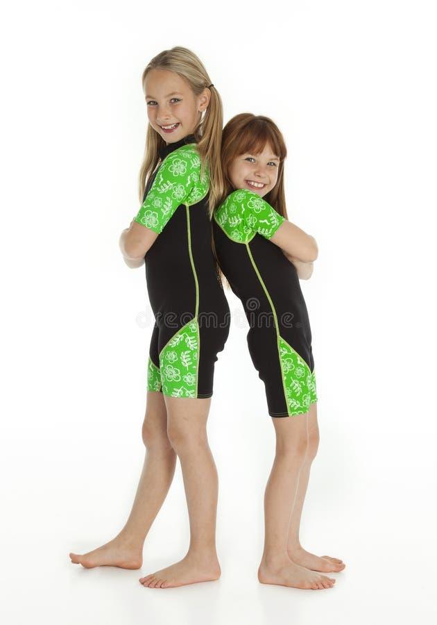 Zwei kleine Mädchen, die zurück zu hinteren tragenden Wetsuits stehen lizenzfreies stockbild