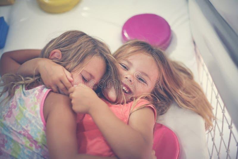 Zwei kleine Mädchen im Spielplatz Kaukasische Mädchen, die auf Boden a liegen lizenzfreies stockbild