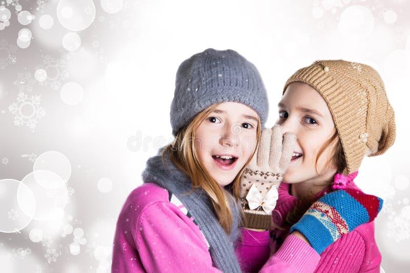 Zwei kleine Mädchen im Weihnachtshintergrund lizenzfreie stockfotografie