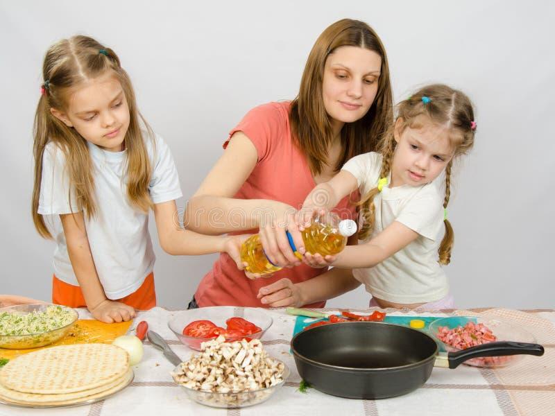 Zwei kleine Mädchen am Küchentisch mit der Begeisterung, zum meiner Mutter zu helfen, Pflanzenöl in einer Bratpfanne zu gießen lizenzfreie stockfotos