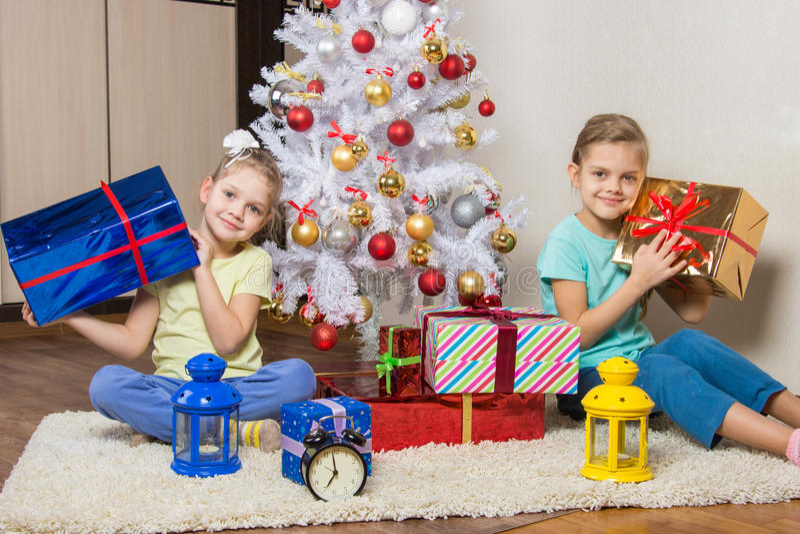 Zwei kleine Mädchen mit den Weihnachtsgeschenken früh morgens sitzend durch den Weihnachtsbaum lizenzfreies stockfoto