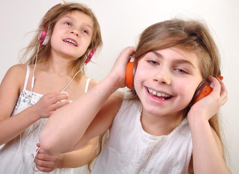Zwei kleine Mädchen mit Kopfhörern hörend Musik stockfotografie