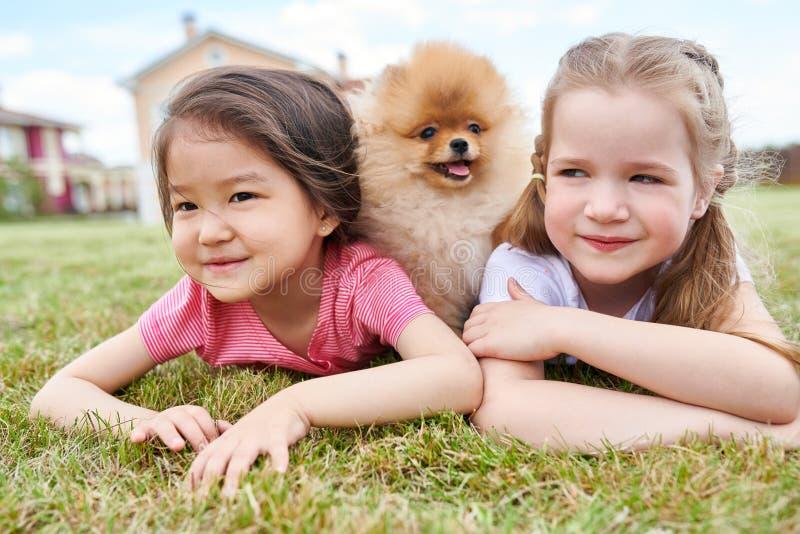 Zwei kleine Mädchen mit nettem Welpen draußen lizenzfreie stockfotos