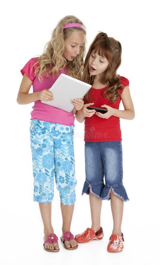 Zwei kleine Mädchen mit Tablette-Einheit lizenzfreies stockbild