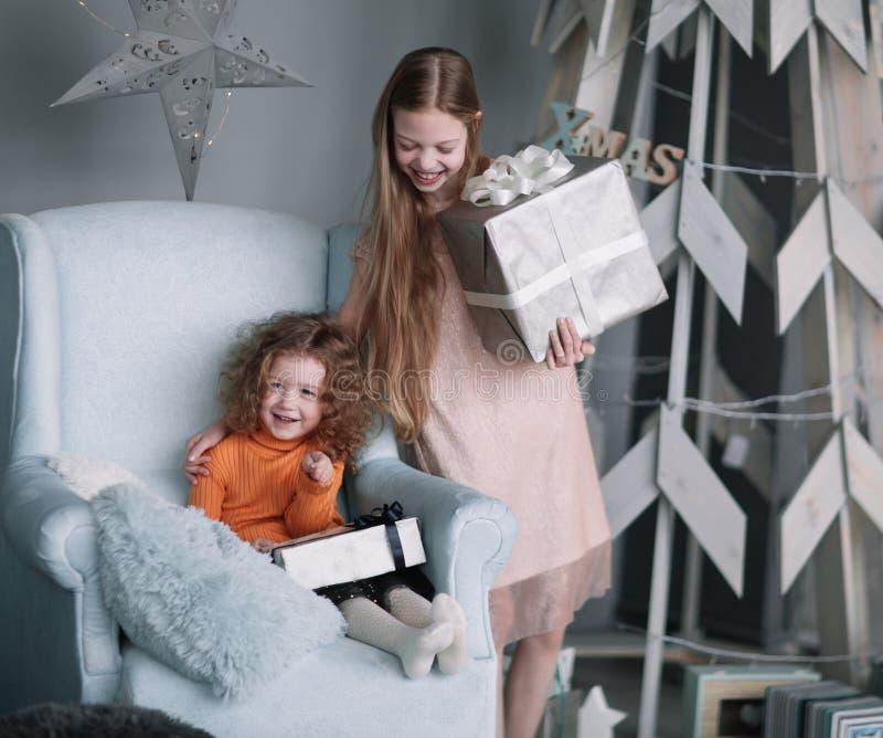 Zwei kleine Mädchen mit Weihnachtsgeschenken auf Weihnachtsabend lizenzfreie stockfotografie