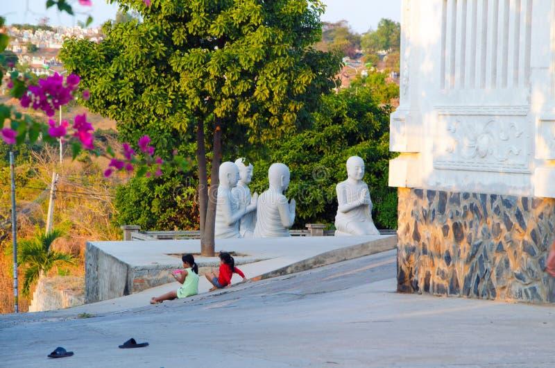 Zwei kleine Mädchen sitzen auf dem Bürgersteig gegen den Hintergrund einer bildhauerischen buddhistischen Zusammensetzung stockfoto