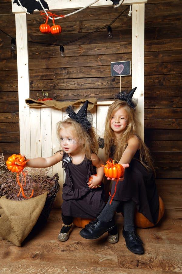 Zwei kleine Schwestern in den Kostümen von den Hexen, die auf einem Kürbis sitzen Das Konzept von Halloween stockfotografie
