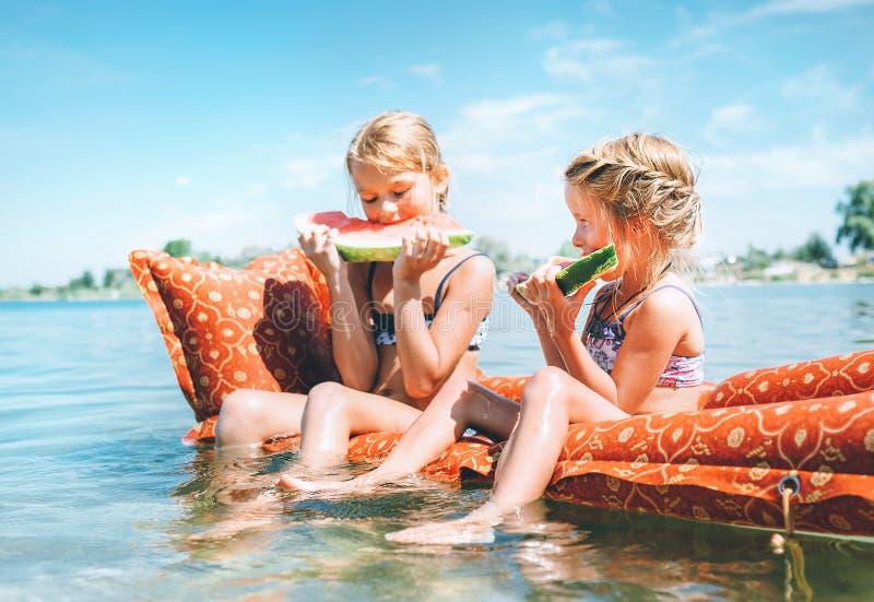 Zwei kleine Schwestern, die auf innflatable mattrace sitzen und Wassermelone essen stockfotos