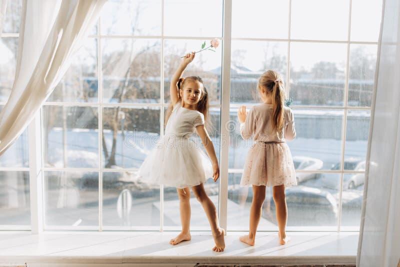 Zwei kleine Schwestern, die in den schönen Kleidern gekleidet werden, stehen auf dem Fensterbrett nahe bei dem Spiegel lizenzfreies stockfoto