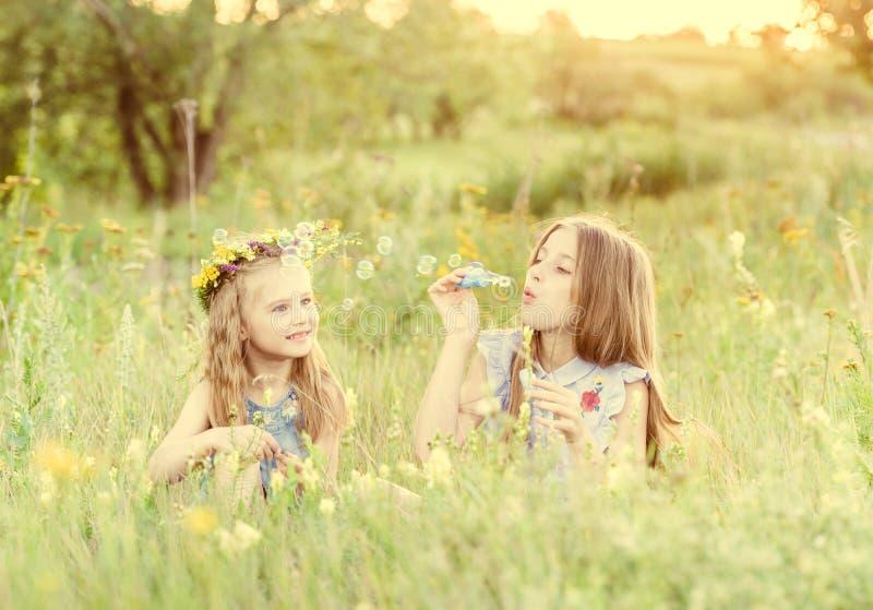 Zwei kleine Schwestern, die Seifenblasen durchbrennen stockfotos