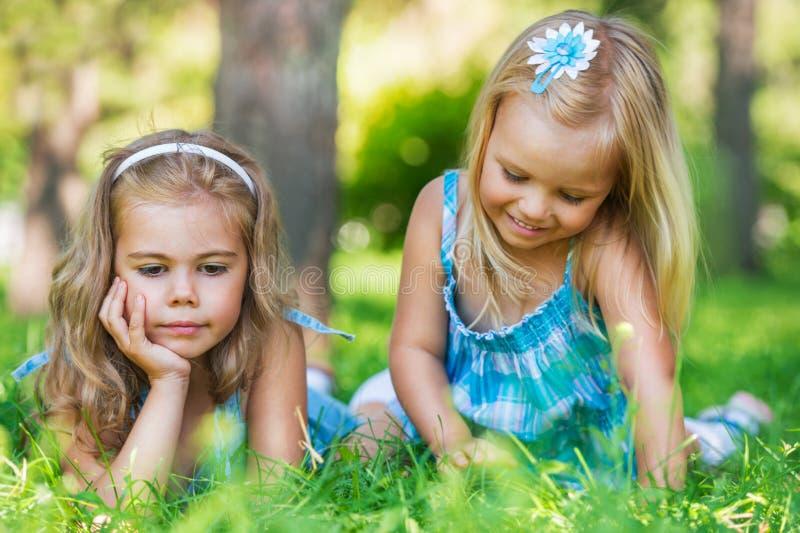 Zwei kleine Schwestern, die Spaß im Sommerpark haben stockbild