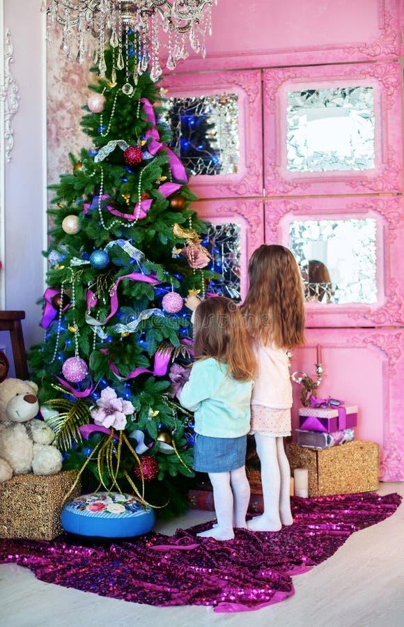Zwei kleine Schwestern, die Weihnachtsbaum verzieren Das Konzept von Chr stockfotografie