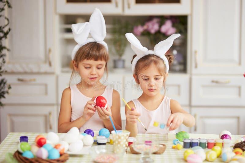 Zwei kleine Schwestern mit den weißen Ohren des Kaninchens auf ihren Köpfen färben die Eier für die Ostern-Tabelle in der gemütli stockfoto