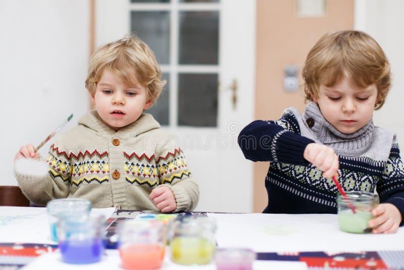 Zwei kleine Zwillingsjungen, die den Spaß Innen, malend mit unterschiedlichem haben lizenzfreie stockfotos
