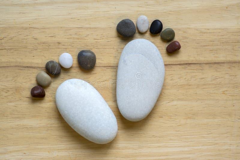 Zwei kleiner Steinfuß und zehn Zehen auf hölzernem Hintergrund, Stein in Form menschlichen Füße stockfoto