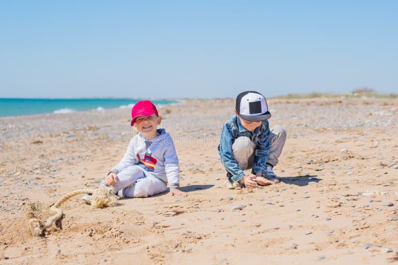 Zwei Kleinkinder, die Spielwaren im Sand spielen lizenzfreie stockfotografie