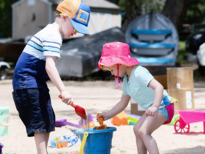 Zwei Kleinkinder, ein Junge u. ein Mädchen, gekleidet mit gutem Sonnenschutz, Spiel auf Sandy Beach Building Sand Castles lizenzfreie stockfotografie