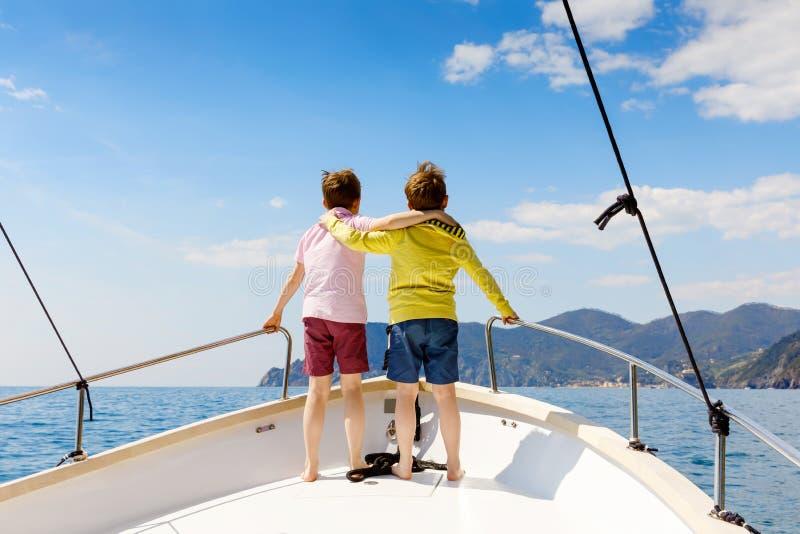 Zwei Kleinkindjungen, die besten Freunde, die Segelboot genie?en, l?sen aus Familienurlaube auf Ozean oder Meer am sonnigen Tag K lizenzfreies stockbild