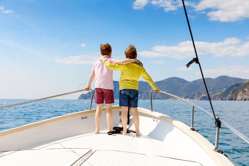 Zwei Kleinkindjungen, die besten Freunde, die Segelboot genie?en, l?sen aus Familienurlaube auf Ozean oder Meer am sonnigen Tag K stockbild