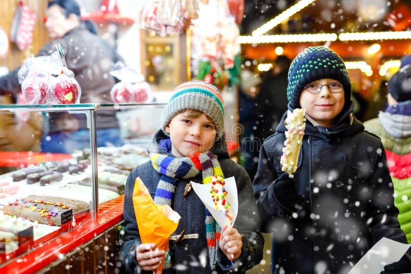 Zwei Kleinkindjungen, die netten Geschwister, welche die Bananen bedeckt werden mit Schokolade essen, die marshmellows und buntes lizenzfreies stockbild