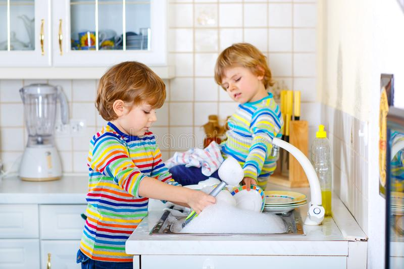 Zwei Kleinkindjungen, die Teller in der inländischen Küche waschen lizenzfreies stockbild